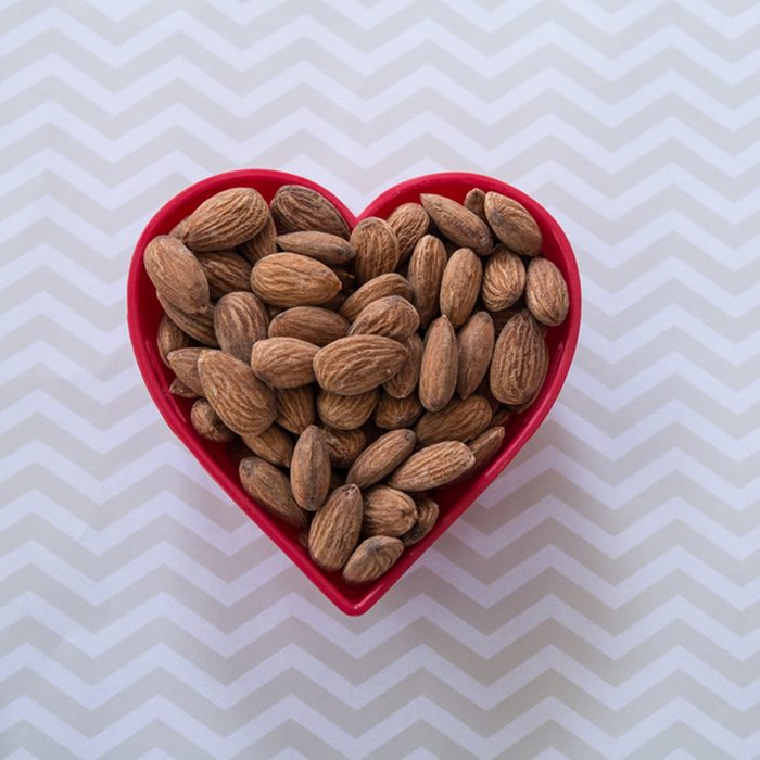 Snack of almonds in red heart shaped bowl on chevron patterned background