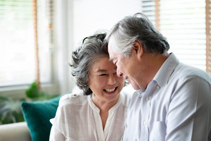 Asian senior couple in love laughing and having fun at their house. Anniversary. Copy space.