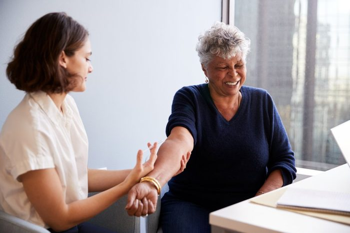 Senior Woman Being Vaccinated With Flu Jab By Female Doctor In Hospital Office