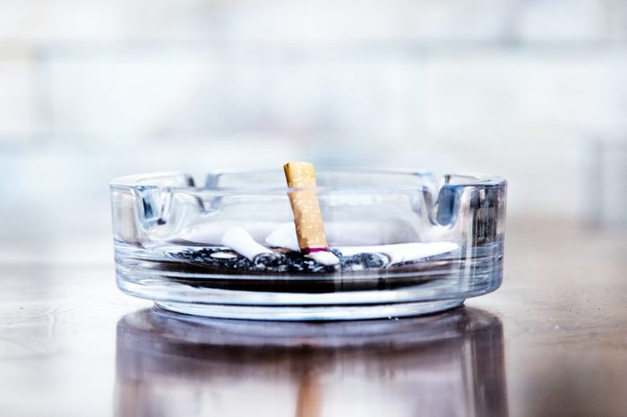 Cigarette butts and ashtray in a glass, leave off smoking.