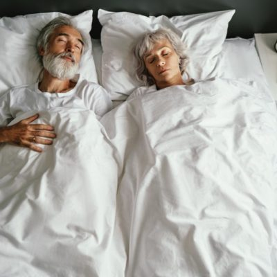 Senior family couple sleeping together in bed.