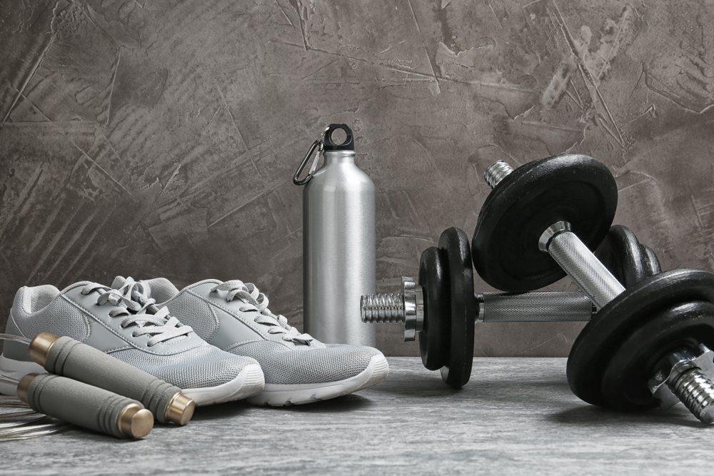 Composition with dumbbells and fitness accessories on floor