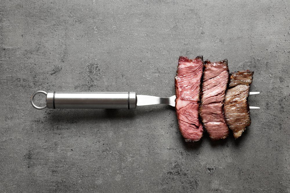 Fork with pieces of delicious barbecued meat on gray background, top view