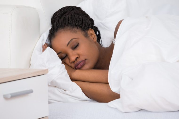 Portrait Of A Young African Woman Sleeping On Bed