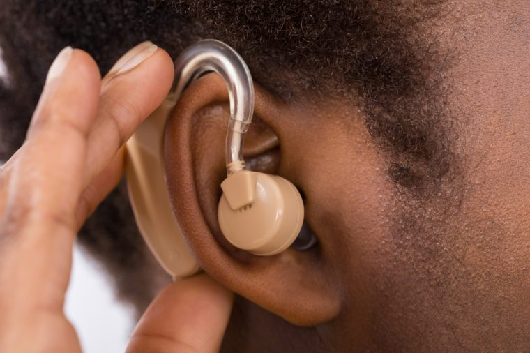 Close-up Of African Woman Wearing Hearing Aid In Ear