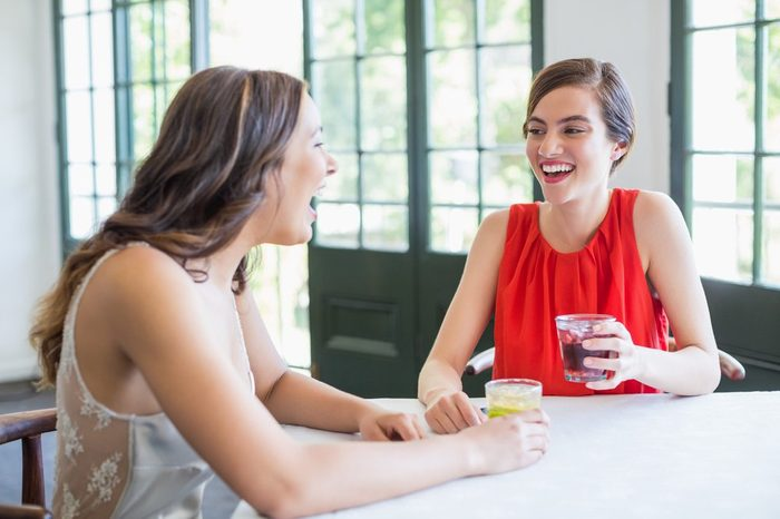 Friends laughing while having cocktails in the restaurant
