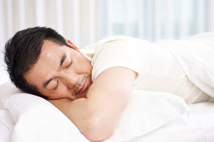 asian man lying on front in bed sleeping.