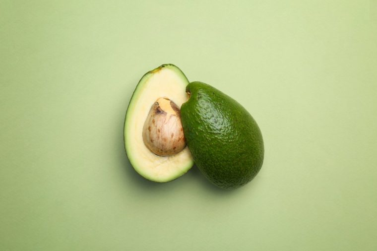 Cut avocado on color background, top view