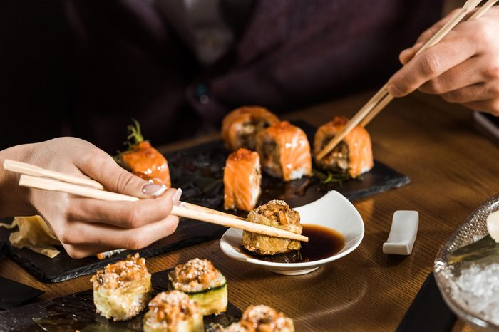 Cropped view of people eating sushi with chopsticks in restaurant