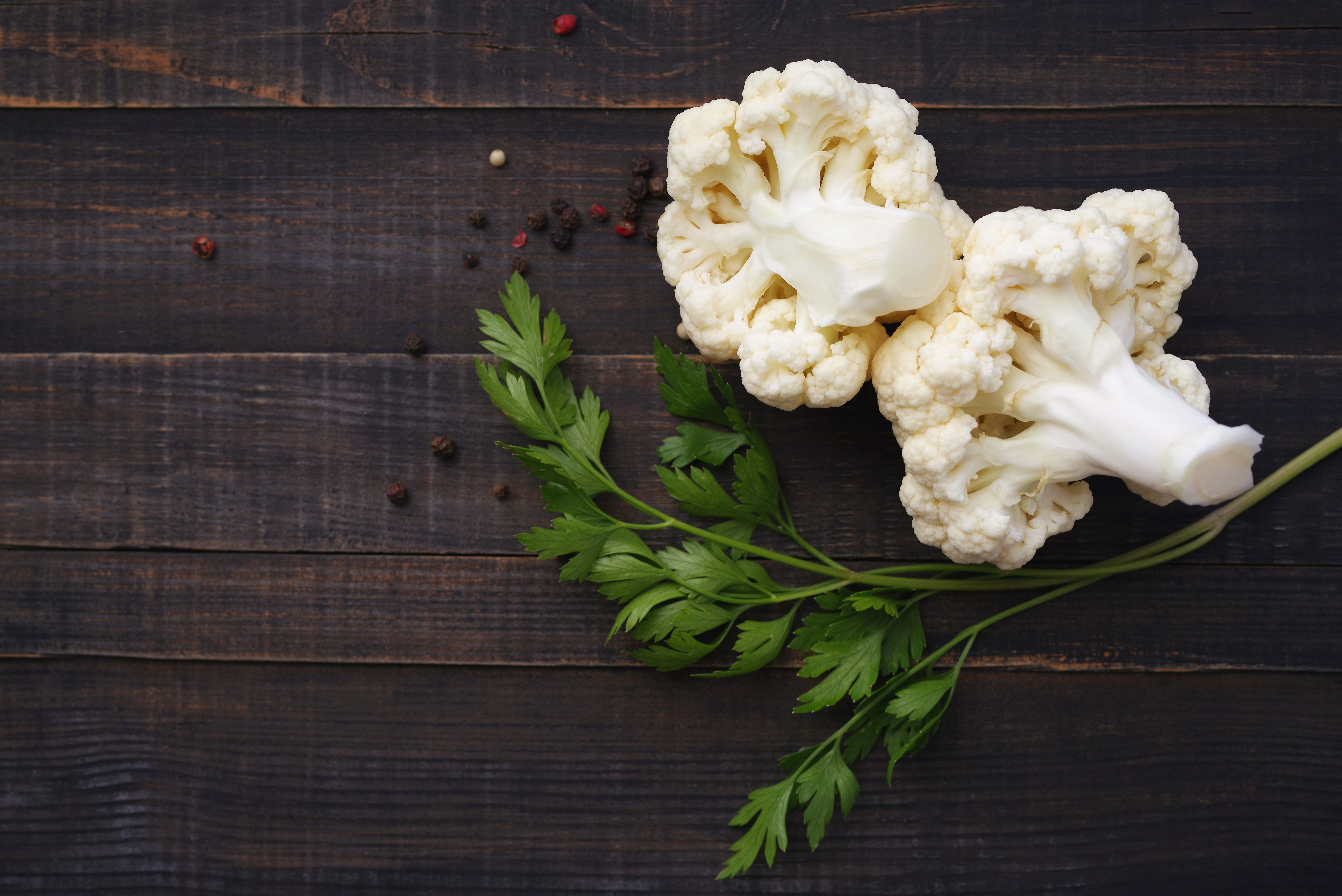 Fresh cauliflower and greens of parsley on a wooden surface close up, soft focus