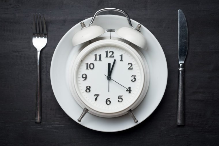Weight loss or diet concept,Alarm clock on plate with knife and fork on wood