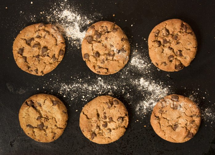 Two rows of freshly baked chocolate chips cookies with flour, shot from above on an old black baking tray