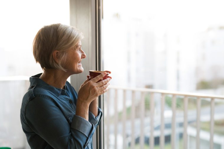 Senior woman at the window holding a cup of coffee