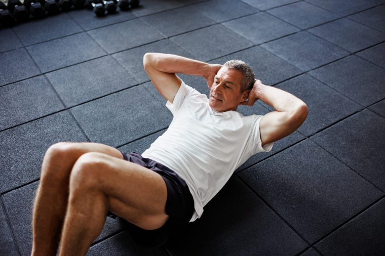 Focused senior man in sportswear doing sit ups alone while working out on the floor of a gym