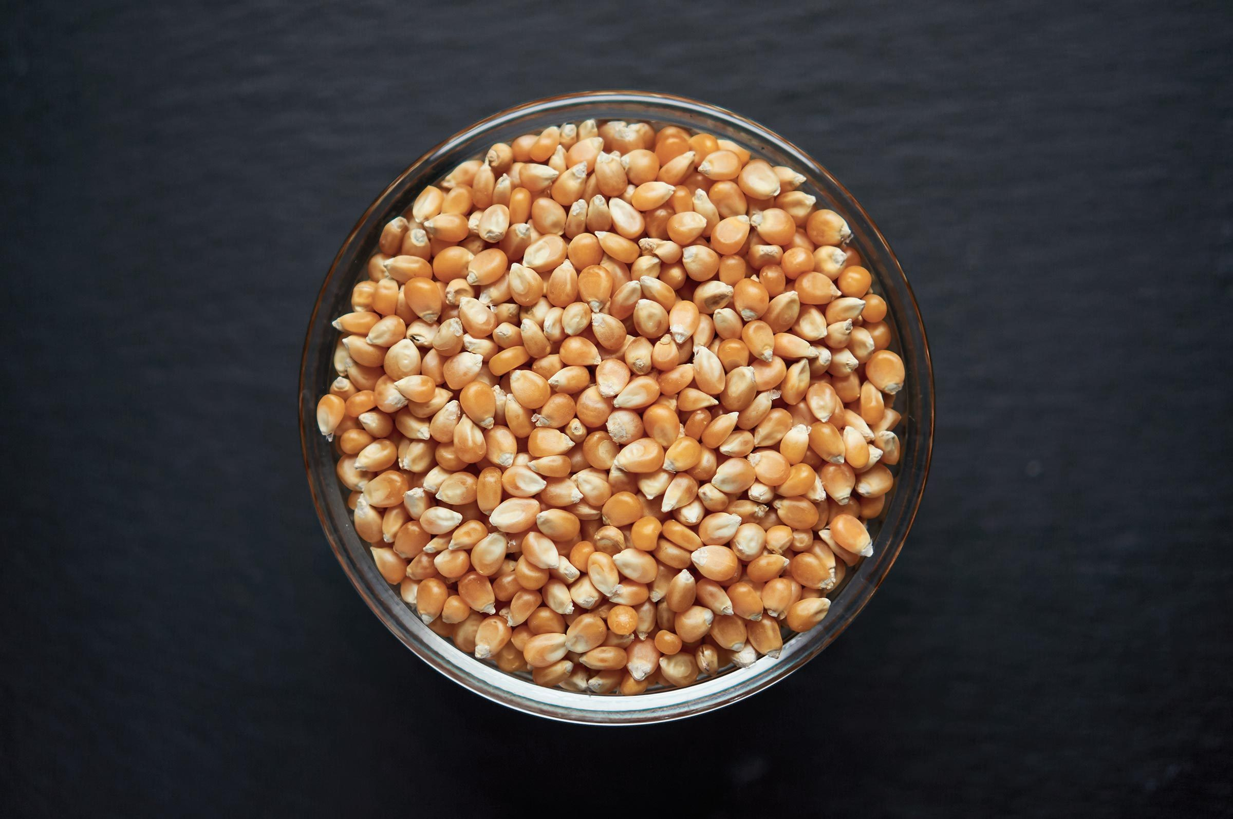 Corn seeds in a bowl on dark background. Vegetarian organic food.