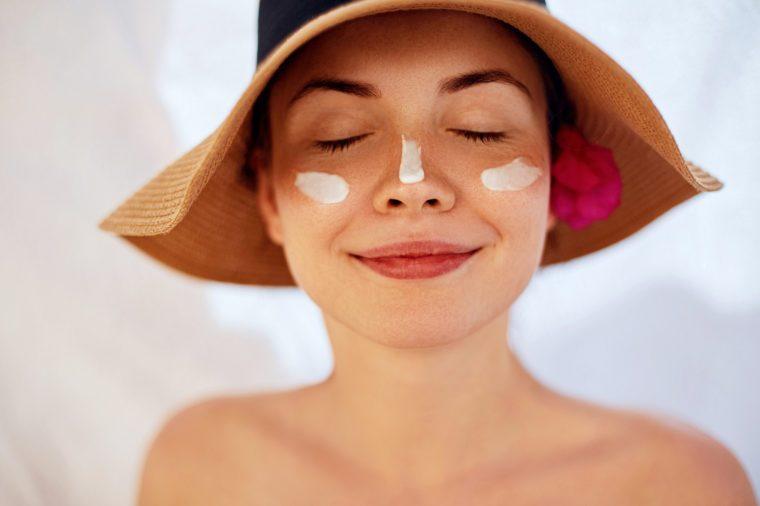 Woman smile applying sun cream on face. Skincare. Body Sun protection. sunscreen. Female in hat smear moisturizing lotion on skin.