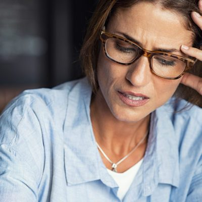 Portrait of stressed mature woman with hand on head looking down. Worried woman wearing spectacles. Tired lady having headache sitting indoors.