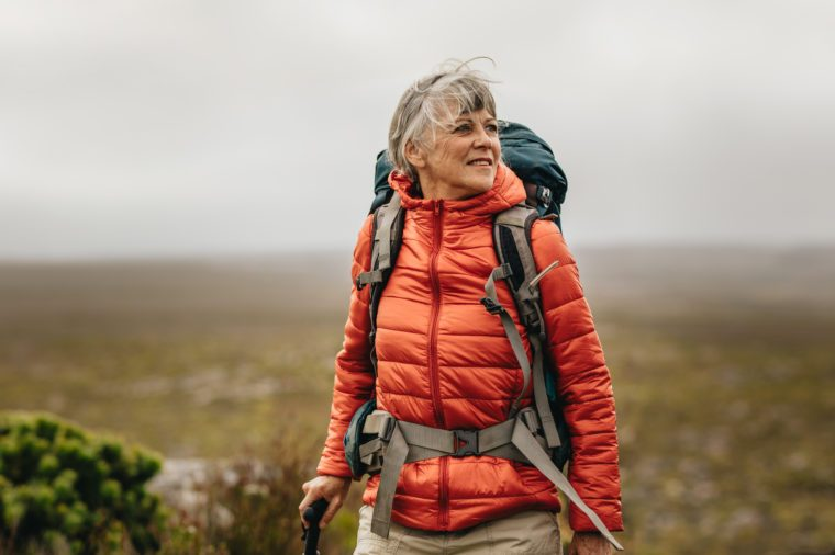 Woman walking on a hill holding a trekking pole. Woman wearing jacket and backpack on a trekking expedition.