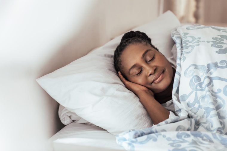 Content young African woman sleeping peacfully under a duvet in her bed at home in the early morning