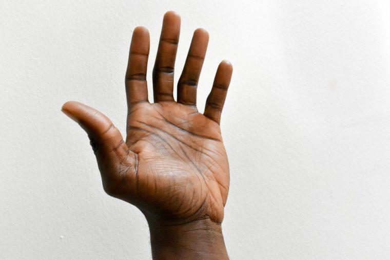 left hand of dark skin African man isolated on white background