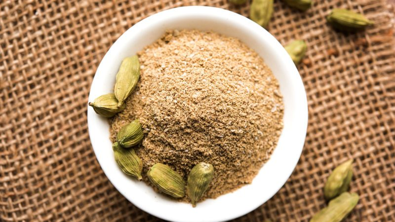 elaichi or Cardamom powder in bowl or heap over moody background with pods.