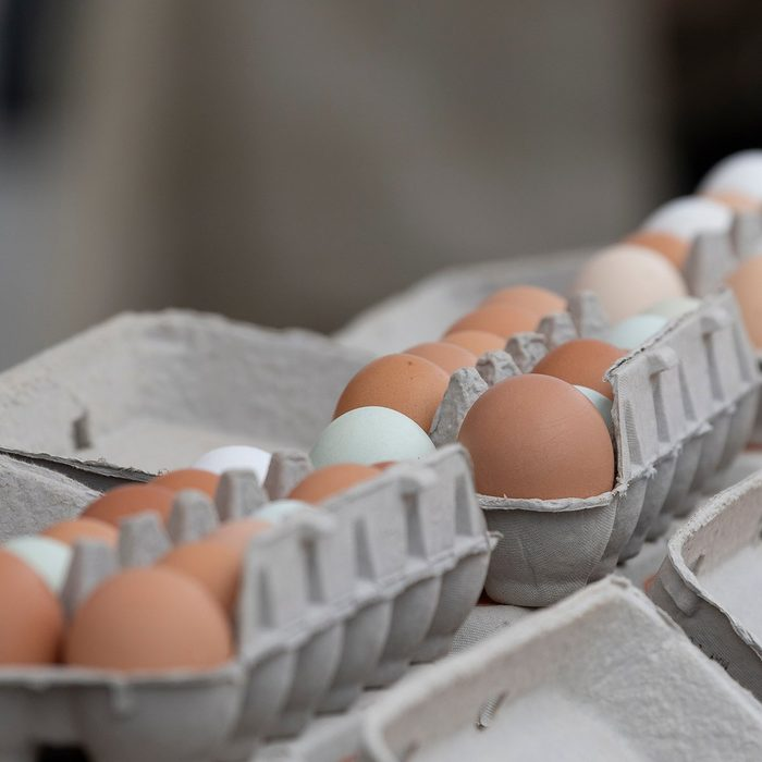 Gray cardboard cartons of brown, green and white chicken eggs for sale at a farmer's market.