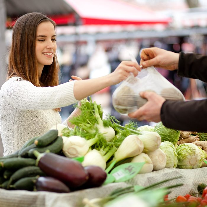 Millennial young woman buying fresh vegetables at farmer's market