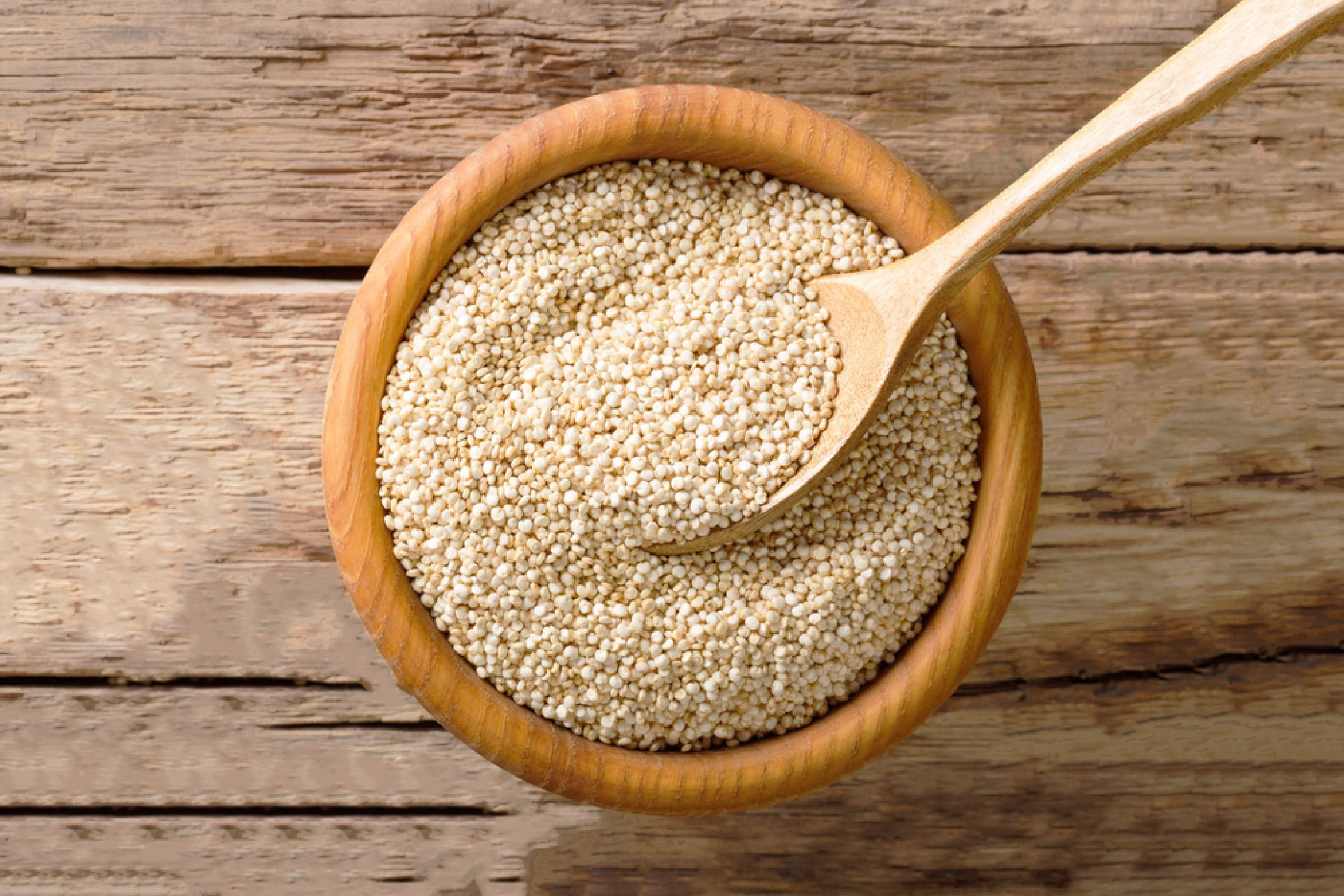 Raw quinoa close up in a wooden bowl on the table. top view from above horizontal background