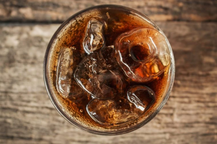 Cola in glass with ice from top view on table.