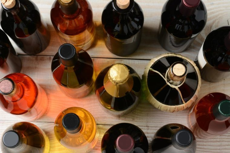 High angle shot of assorted wine and champagne bottles on a rustic wood table. Horizontal format.