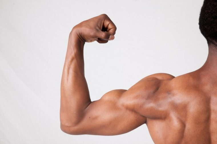 Strong Black man flexing his arm, from the back
