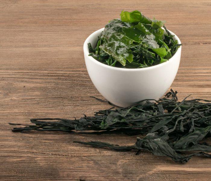 Heap of Dry Wakame Seaweed on Wooden Background. Healthy Algae Food
