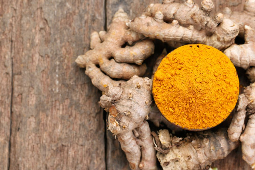 Turmeric powder and turmeric on wooden background.View from the top.