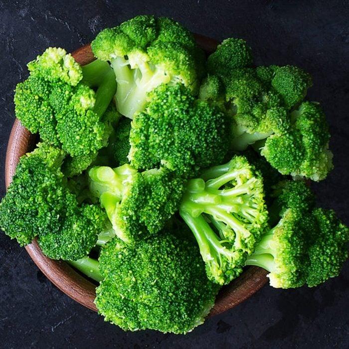 Fresh raw broccoli in a wooden bowl on a dark background