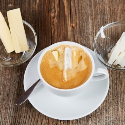 Coffee, butter and coconut oil for bulletproof coffee on a brown wooden table