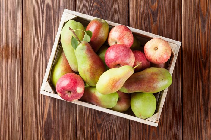 Pears and apples in wooden box on table. Top view