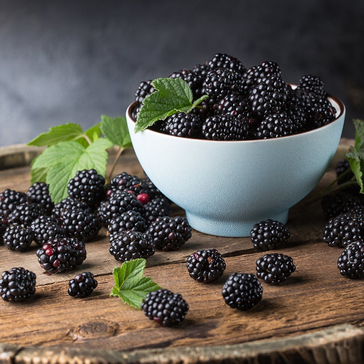 Ripe blackberries with leaves in a bowl on a wooden board on a dark background