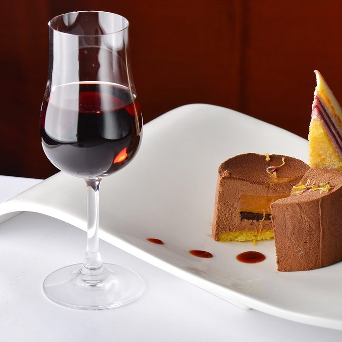 Chocolate and berries cake with glass of dessert wine
