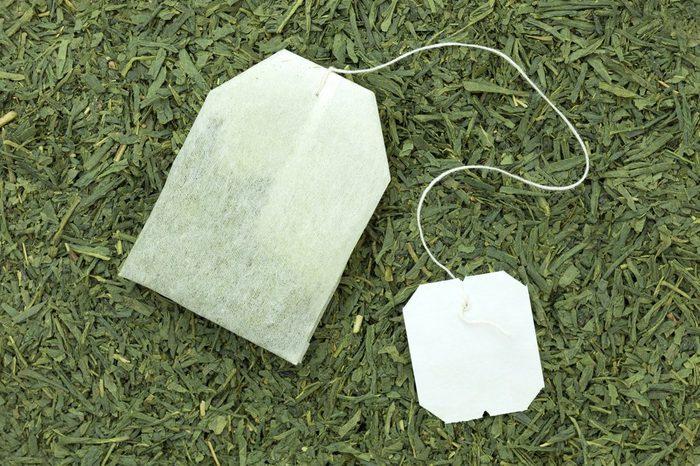green tea bag on tea leaves