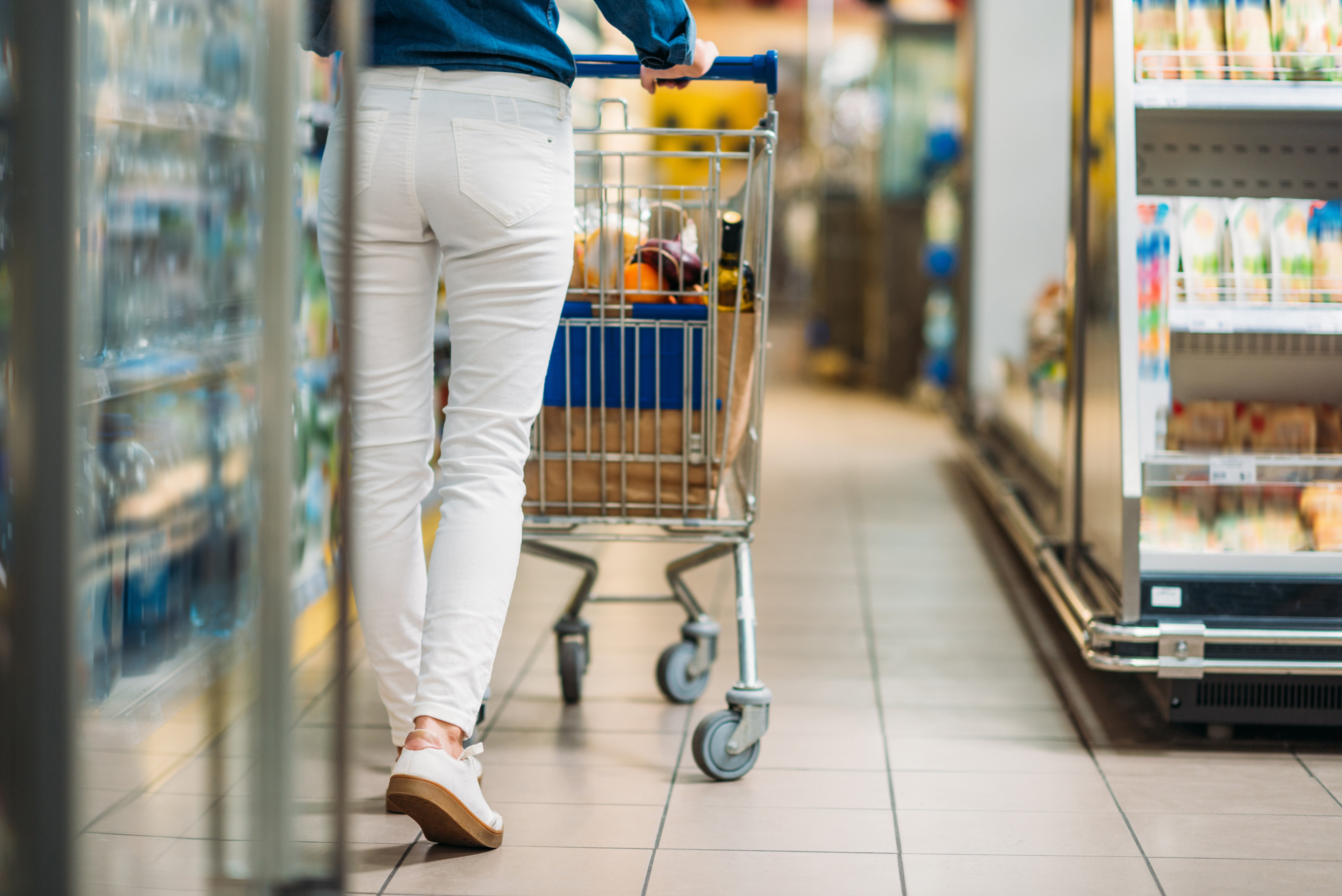 cropped shot of woman with shopping cart walking in supermarket