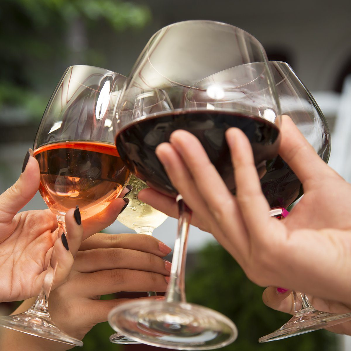 Group of unrecognizable people celebrating while holding wine glasses and toasting.