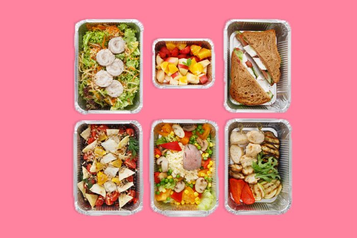 Healthy food delivery, daily meals and snacks. Diet nutrition, vegetables, meat and fruits in foil boxes. Top view, flat lay at white wood with copy space