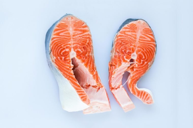 two steaks of salmon on a white cutting board on wooden background, top view.
