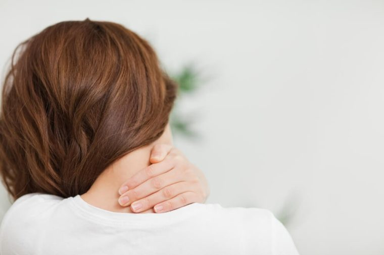 Close up of a brunette woman massing her neck in a room
