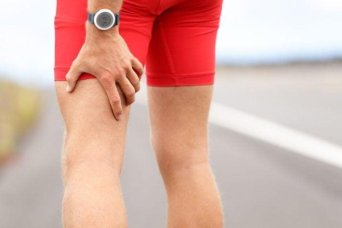 Hamstring sprain or cramps. Running sports injury with male triathlete runner.