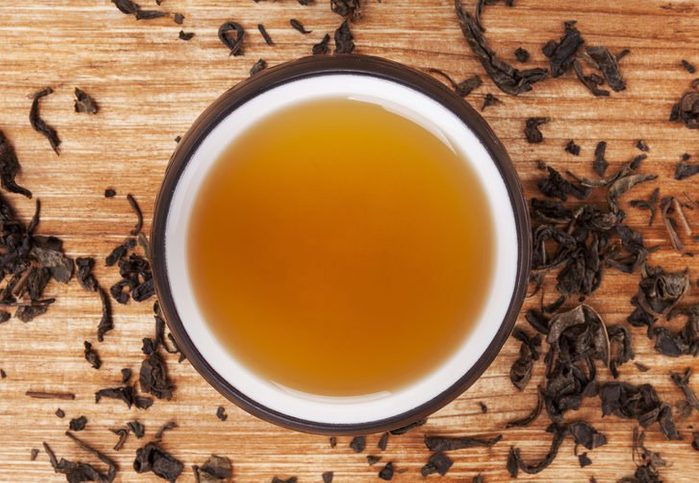 Mug of hot delicious green tea surrounded with dried leaves on wooden background. Delicious oriental beverage.