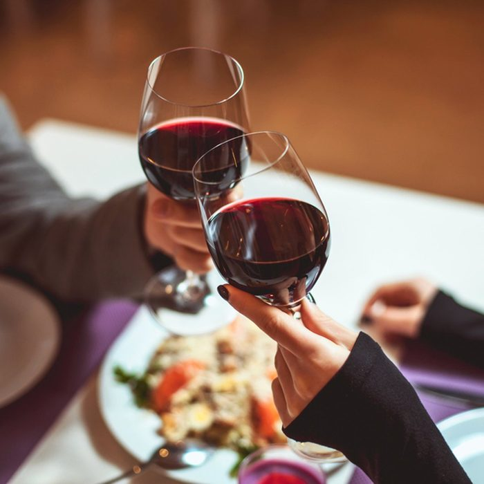 Beautiful young couple with glasses of red wine in luxury restaurant; Shutterstock ID 364873787