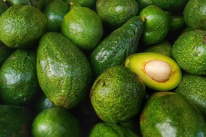 Bunch of green Avocados. One of them is opened that the stone and the pulp are visible.