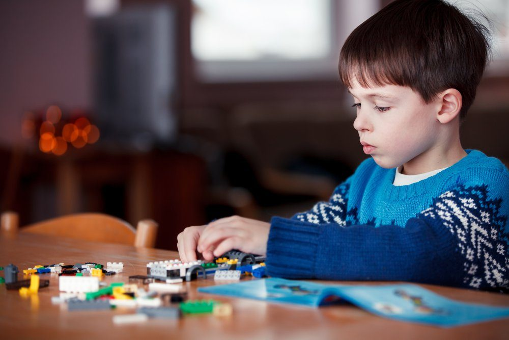 Five years old boy playing with building blocks, first education role lifestyle
