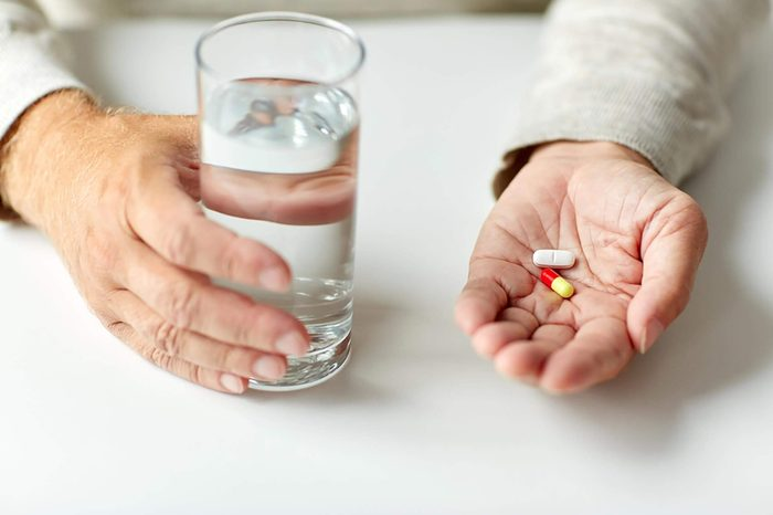 age, medicine, healthcare and people concept - close up of senior man hands with pills and water